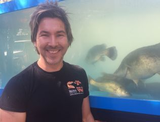 Zoologist and TV presenter Chris Humfrey, who ran river wildlife education sessions at the competition, next to a tank holding Spotted Bess, photo by Adele Rohde